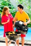 Couples asiatiques ayant le barbecue à la piscine Photographie stock