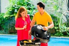 Couples asiatiques ayant le barbecue à la piscine Photos stock