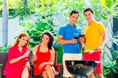 Couples asiatiques ayant le barbecue et buvant du vin Photographie stock