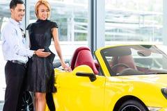 Couples asiatiques choisissant la voiture de roadster au concessionnaire images libres de droits