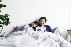 Couples asiatiques détendant sur le lit ensemble photo stock