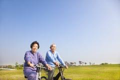 Couples asiatiques d'aînés faisant du vélo en parc Photographie stock