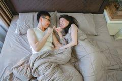 Couples asiatiques dans l'amour, dormant ensemble sur le lit la nuit image libre de droits
