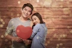 Couples asiatiques de sourire dans l'amour tenant le symbole rouge de coeur Photographie stock libre de droits