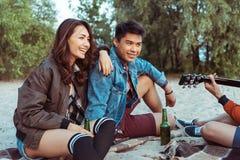 Couples asiatiques de sourire se reposant sur la plage sablonneuse et écoutant leur ami jouant la guitare Image libre de droits
