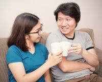 Couples asiatiques doux se reposant en café potable de sofa Photos libres de droits