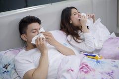 Couples asiatiques en difficulté éternuant dans le lit image stock