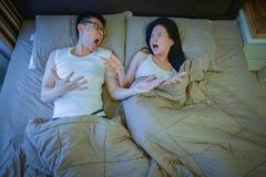 Couples asiatiques fâchés combattant sur le lit la nuit photo stock
