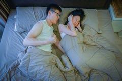 Couples asiatiques fâchés combattant sur le lit la nuit image stock