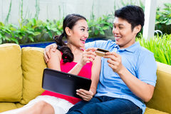 Couples asiatiques faisant des emplettes en ligne dans l'Internet avec l'ordinateur portable Photos stock