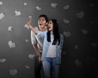 Couples asiatiques faisant le selfie avec le téléphone portable Photographie stock libre de droits