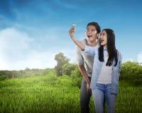 Couples asiatiques faisant le selfie avec le téléphone portable Photo libre de droits