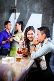 Couples asiatiques flirtant et buvant à la barre de boîte de nuit Image libre de droits