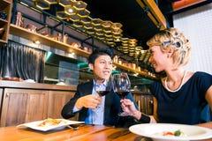 Couples asiatiques grillant avec du vin Image stock