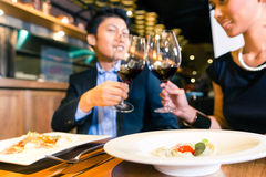 Couples asiatiques grillant avec le vin rouge Photographie stock libre de droits