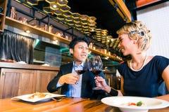 Couples asiatiques grillant avec le vin rouge Photo libre de droits