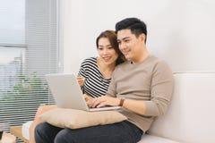 Couples asiatiques heureux dans l'amour surfant sur l'ordinateur portable à la maison Images stock