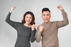 Couples asiatiques heureux de sourire tenant les deux pouces  Images libres de droits