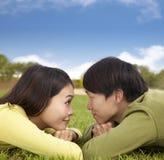Couples asiatiques heureux se trouvant sur l'herbe Photographie stock libre de droits
