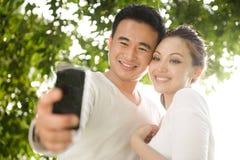 Couples asiatiques prenant des photographies Images stock