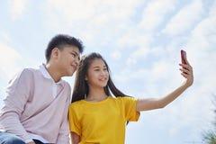 couples asiatiques prenant un selfie extérieur photo stock