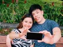 Couples asiatiques prenant une photo de selfie dans la scène extérieure de parc - amour Image stock