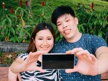 Couples asiatiques prenant une photo de selfie dans la scène extérieure de parc - amour Photo libre de droits