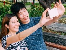 Couples asiatiques prenant une photo de selfie dans la scène extérieure de parc - amour Photos libres de droits