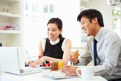 Couples asiatiques regardant l'ordinateur portable au-dessus du petit déjeuner Images stock