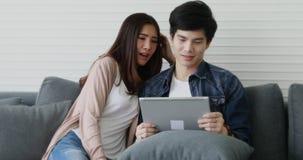 Couples asiatiques se reposant sur le sofa et parler banque de vidéos