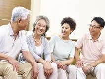 Couples asiatiques supérieurs heureux causant à la maison Image libre de droits
