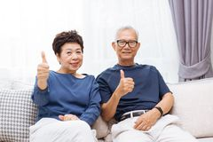 Couples asiatiques supérieurs regardant l'appareil-photo et renonçant à des pouces tout en se reposant sur le sofa à la maison Images libres de droits