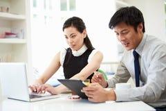 Couples asiatiques utilisant des dispositifs de Digital au Tableau de petit déjeuner Images libres de droits