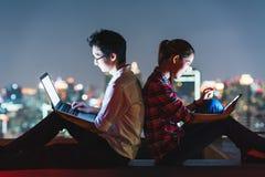 Couples asiatiques utilisant l'ordinateur portable et le smartphone ensemble, maigre sur l'un l'autre sur le dessus de toit la nu Photo stock