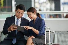 Couples asiatiques utilisant la Tablette dans l'aéroport Photo stock