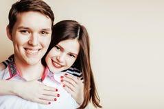 Couples assez adolescents de jeunes, type de hippie avec son sourire heureux d'amie et étreindre sur le fond blanc Photos stock