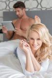Couples assez jeunes de macro sur le lit regardant l'appareil-photo image libre de droits