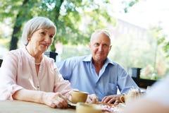 Couples assez supérieurs en café extérieur Photo stock