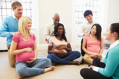 Couples Attending Ante Natal Class Together. Looking At Instructor Sitting On Floor Royalty Free Stock Image