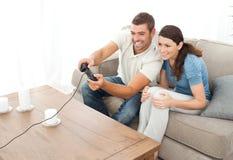 Couples attentifs jouant le jeu vidéo ensemble Photographie stock libre de droits