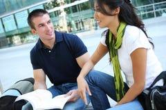 Couples attrayants à la bibliothèque d'école images stock