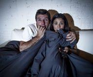 Couples attrayants à la maison appréciant observant la bâche de film d'horreur de télévision avec la couverture Photos stock
