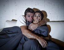 Couples attrayants à la maison appréciant observant la bâche de film d'horreur de télévision avec la couverture Photos libres de droits