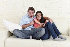 Couples attrayants ayant l'amusement à la maison appréciant observant l'exposition de film d'horreur de télévision Photos libres de droits