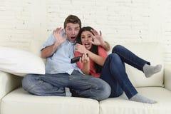 Couples attrayants ayant l'amusement à la maison appréciant observant l'exposition de film d'horreur de télévision Image libre de droits