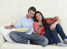 Couples attrayants ayant l'amusement à la maison appréciant observant l'exposition de film d'horreur de télévision Images stock