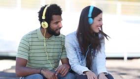 Couples attrayants ayant l'amusement écoutant la musique avec des écouteurs banque de vidéos