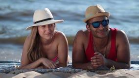 Couples attrayants ayant l'amusement sur la plage banque de vidéos