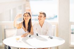 Couples attrayants ayant la première date Café avec un ami Personnes heureuses de sourire faisant un selfie avec un smartphone Image stock
