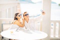 Couples attrayants ayant la première date Café avec un ami Personnes heureuses de sourire faisant un selfie avec un smartphone Photos stock